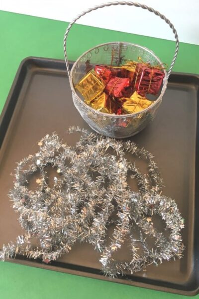 cookie sheet, tinsel, and mini presents, ornaments, or Christmas candy